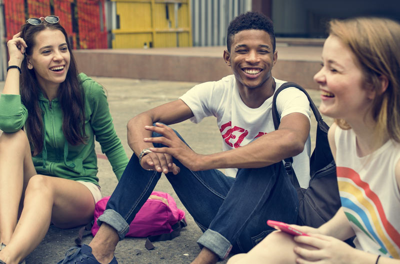 teenagers-sitting-on-ground-laughing